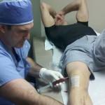Хирург удаляет кровь из колена Джорджа Сент-Пьера